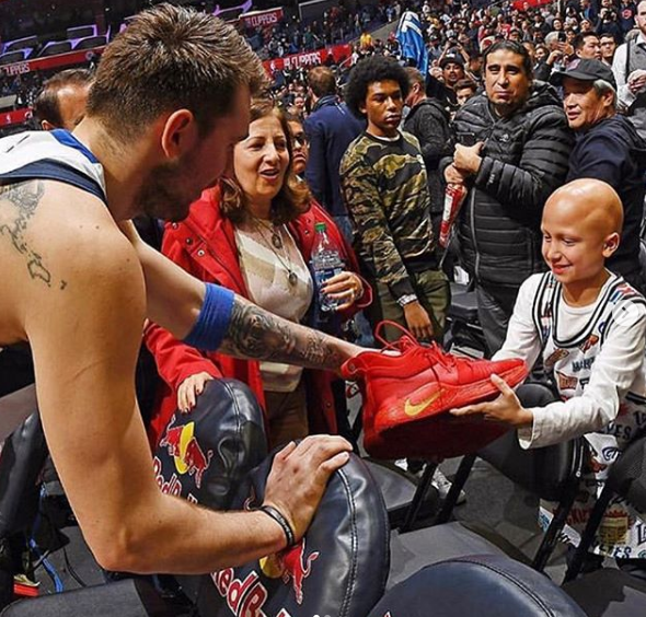 Luka Doncic Giving Shoes To a Child