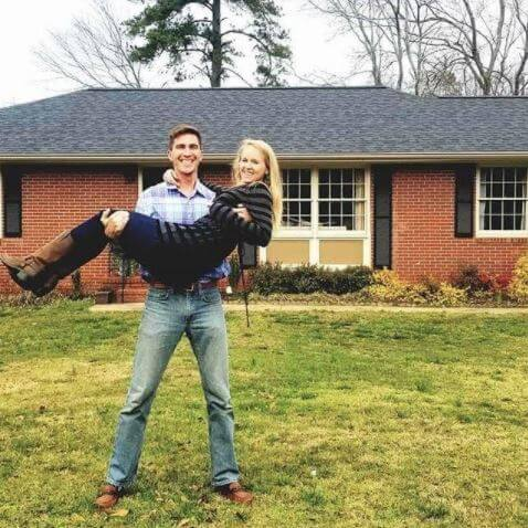 Chris Bruin holding his wife in front of his new home.