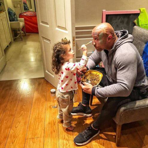 Jasmine Johnson painting her father, Dwayne Johnson's face.