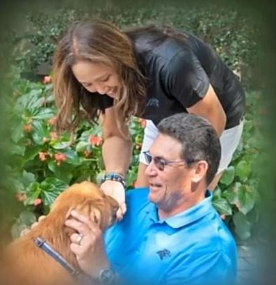 Stephanie Rivera and her husband Ron Rivera playing with their dog